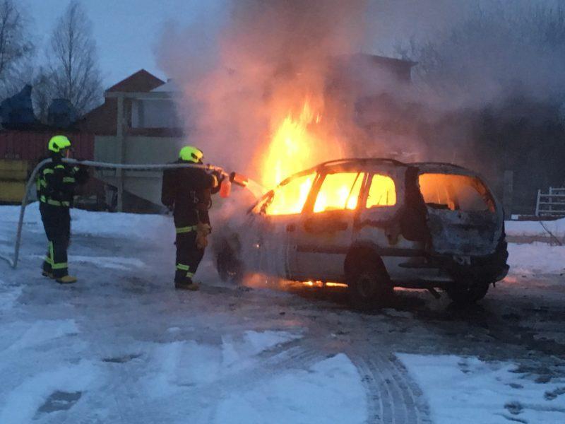 Kaksi palomiestä sammuttaa palavaa autoa