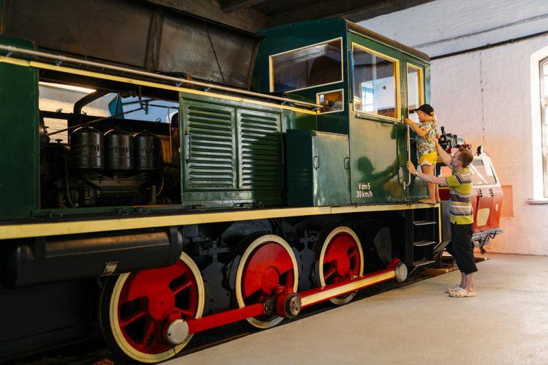 Lapsi ja aikuinen ihmettelemässä vanhaa veturia museossa