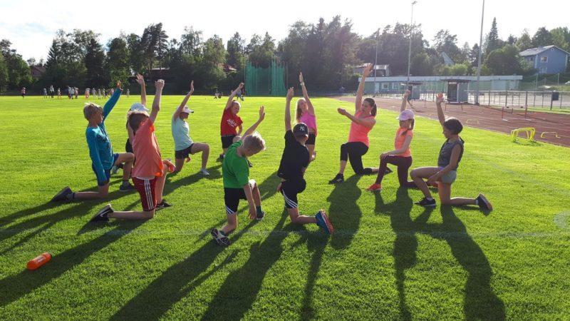 Lapsia urheilukentällä venyttelemässä