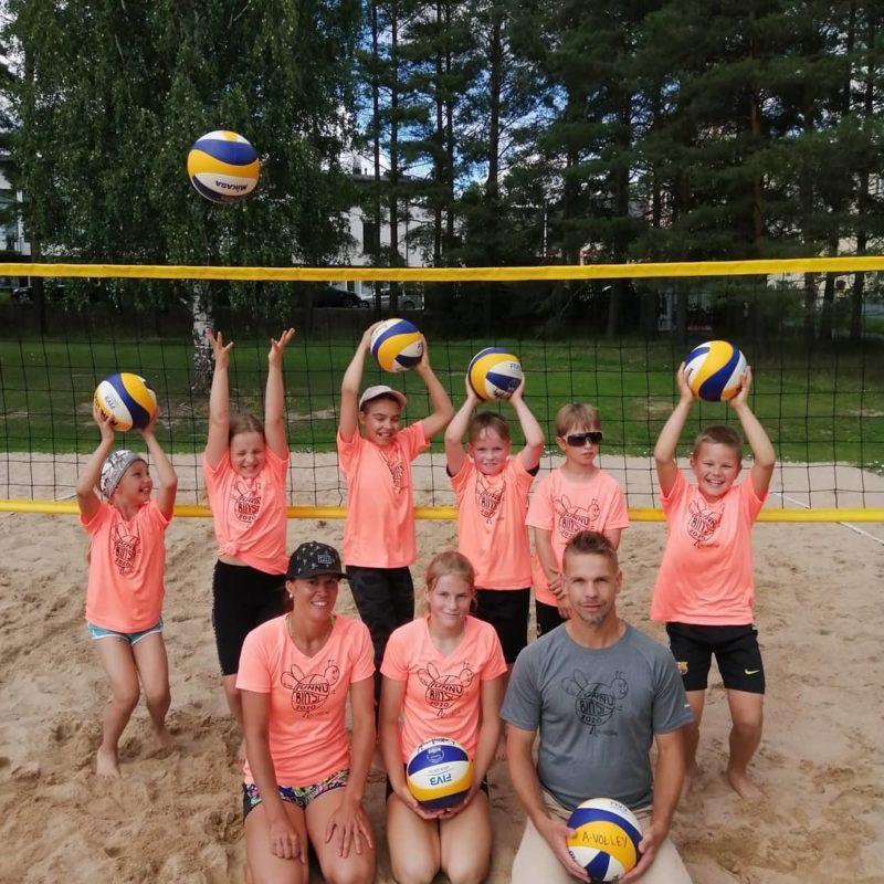 Ryhmäkuva lasten beach-volley joukkueesta ulkokentällä