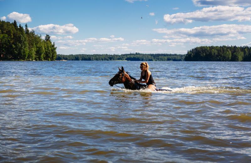 nainen uimassa hevosen kanssa