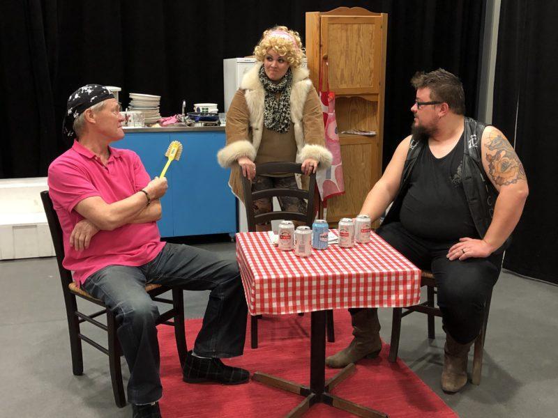 Näyttelijöitä rooleissaan pöydän äärellä.