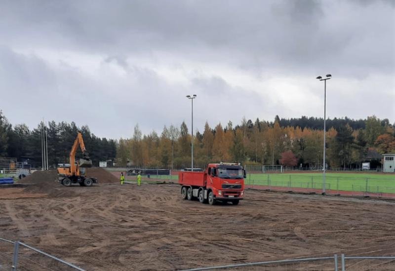 maanrakennuskone urheilukentällä