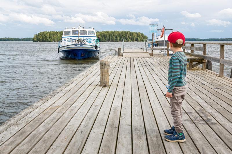 Poika katselee saapuvaa laivaa laiturilla