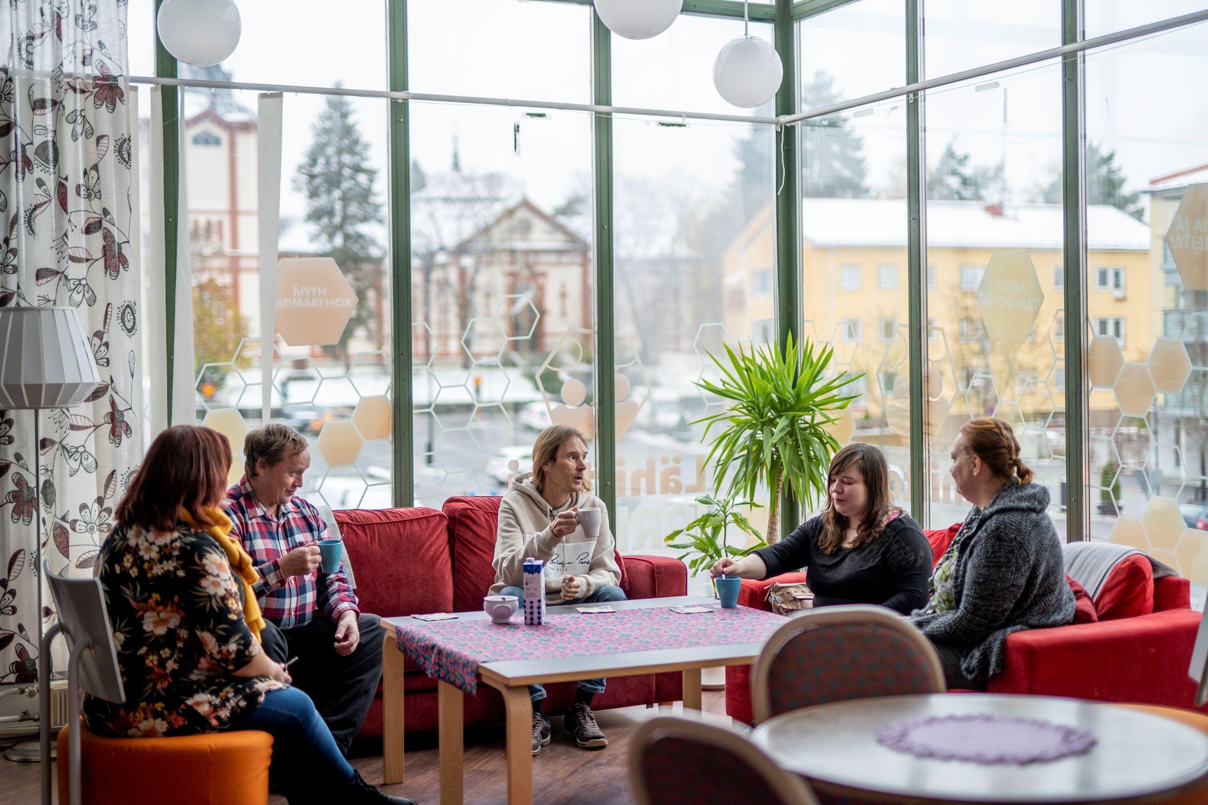 Narikan kävijöitä keskustelemassa sohvilla kahvikupin äärellä