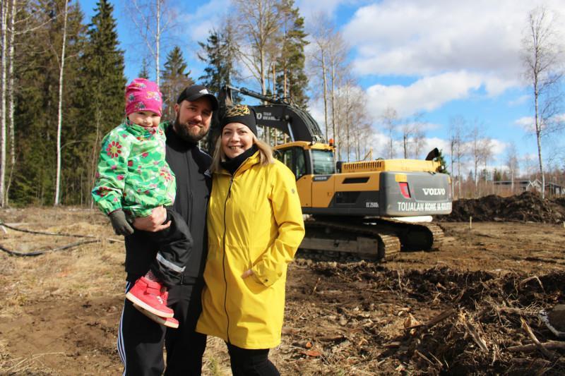 Perhe kaivinkoneen edustalla uudella tontillaan Uusikylässä